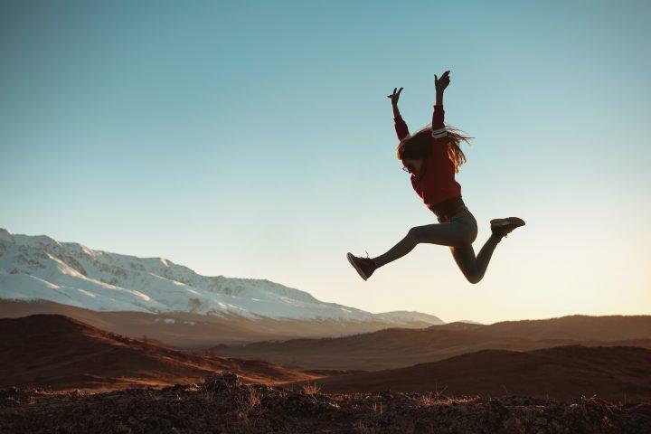 Kobieta w górskim krajobrazie podskakuje w powietrzu
