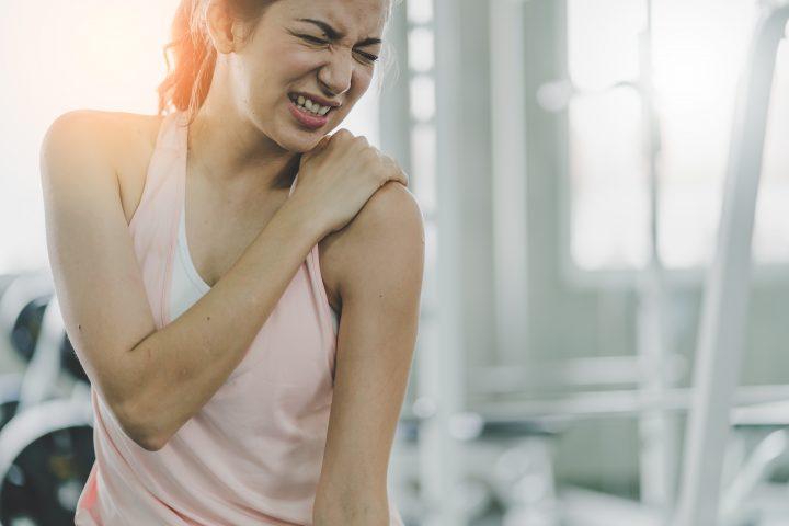 Kobieta trzyma sięza bolące ramię