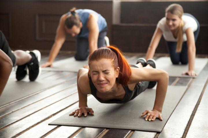 Kobieta ćwicząca na macie z wyrazem bólu na twarzy