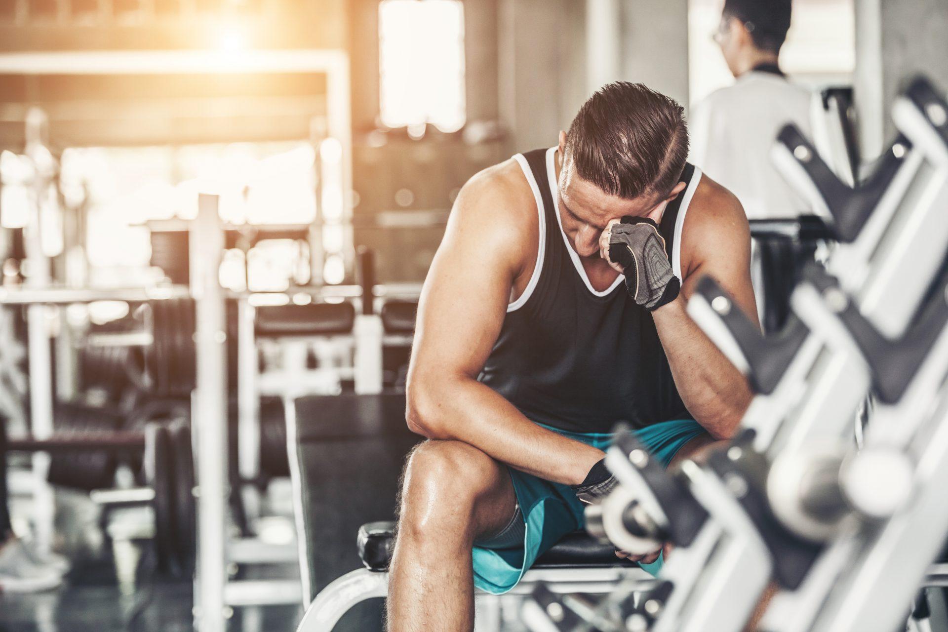 Zmęczony mężczyzna siedzi na siłowni