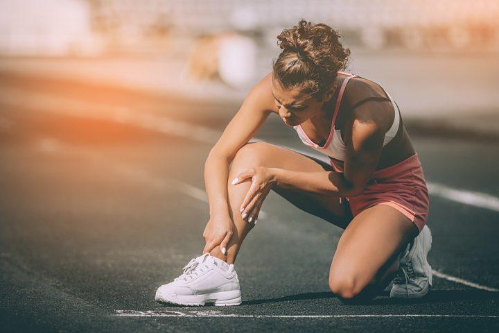 Kobieta z urazem sportowym trzyma się za kostkę
