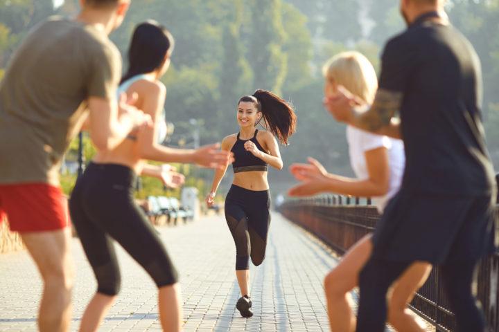Grupa osób dopinguje biegnącą kobietę