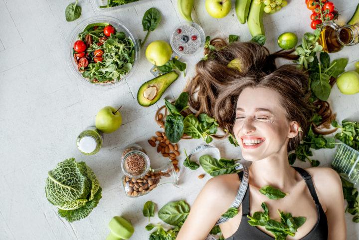 Uśmiechnięta kobieta leży wśród warzyw i owoców