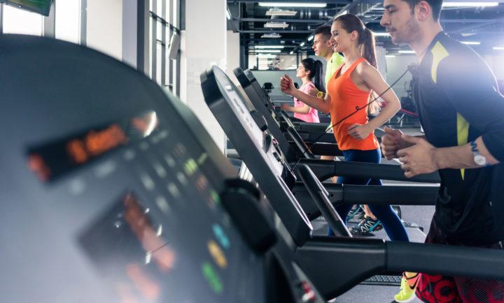Grupa ludzi ćwiczy na siłowni