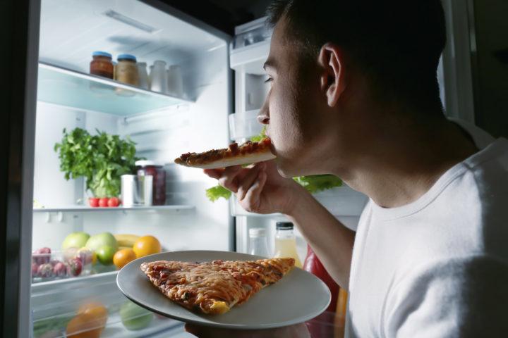 Mężczyzna podjada w nicy pizzę z lodówki
