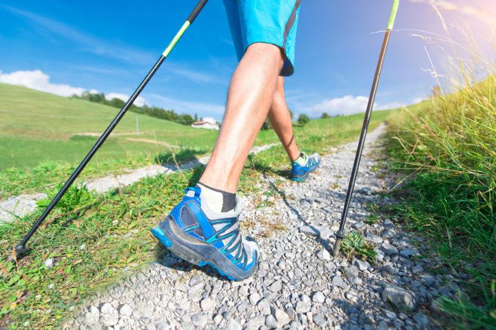 Mężczyzna idący po drodze z kijkami do Nordic Walking