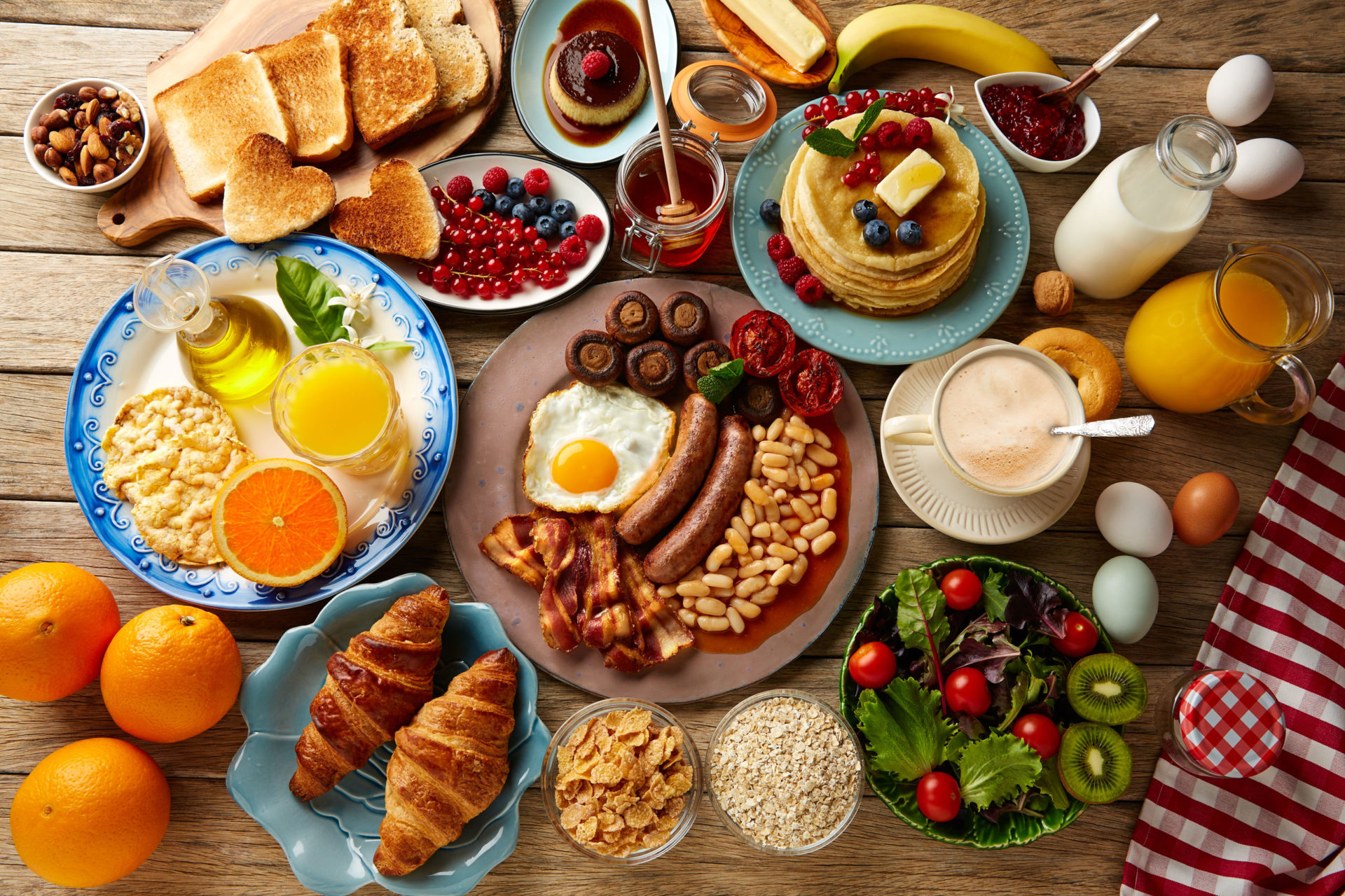 Stół zastawiony najróżniejszymi potrawami: tostami, naleśnikami, sałatkami itp.