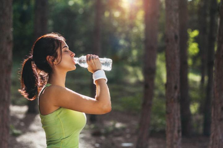 Wysportowana kobieta pije wodę z butelki