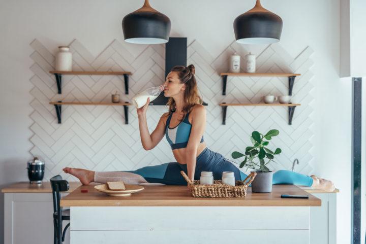 Kobieta w stroju sportowym robi szpagat na blacie kuchennym pijąc mleko
