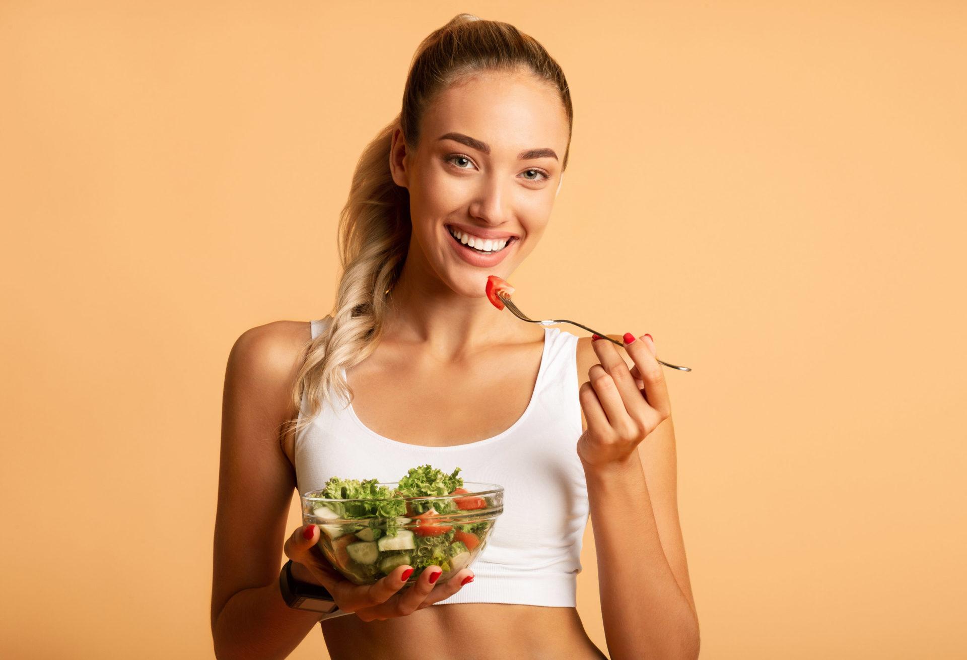 Kobieta w stroju fitness zjada sałatkę